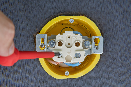 Fixing of new electric socket in household electrical system, an electricians hand with hand screwdriver, close-up.
