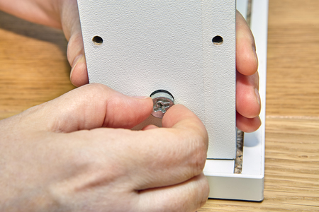 Using flat pack hardware when assembling furniture, installing a drawer with cam lock nut.