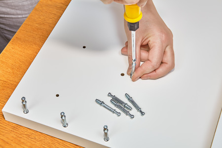 Hands of carpenter is screwing furniture joint connector bolts. Stock Photo