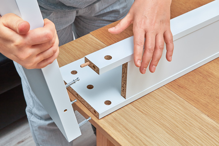 A furniture assembler connects parts of the table with help of wooden dowel pin and connector bolts.