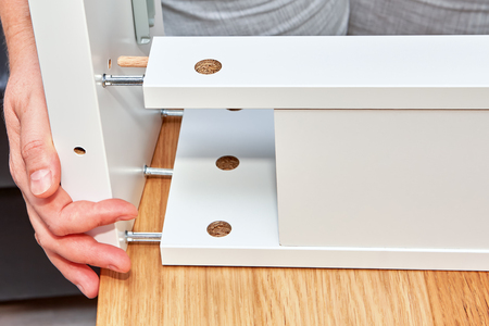 The hands of the furniture assembler join the parts of the table made of particle board, the connection is made with screws and steel cam dowels.