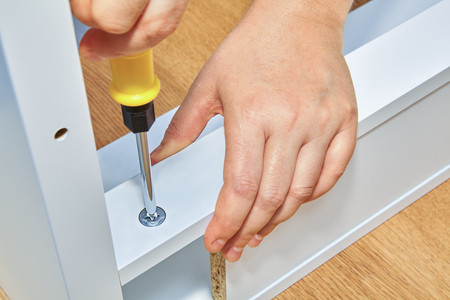 Handyman tightens a nut in a piece of wooden table with a screwdriver, the furniture assembler holds the part of the table with his second hand.