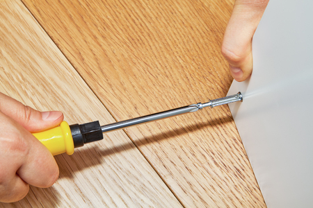 The furniture assembler tightens a cam bolt fixing into the surface of a wooden table made of particle board, flat pack furniture assembly.