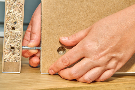 The handyman connects two parts of the table made of particle board with a connecting bolt, flat pack furniture assembly.