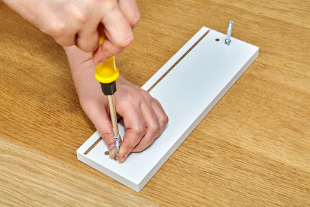 The product assemble tightens the connector bolts with furniture made of chipboard, flat pack furniture assembly service, snap-together joints. Stock Photo