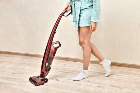 Aspirador de borgoña vertical de mano, con la ayuda de la cual la mujer de la limpieza está aspirando en una habitación vacía. Foto de archivo