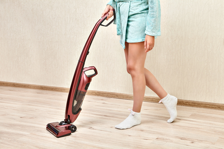Handheld upright burgundy vacuum cleaner, with help of which the cleaning woman is  vacuuming in an empty room.