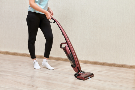 Cleaning woman in black leggins is vacuuming with help of upright vacuum cleaner with led lights on. Foto de archivo
