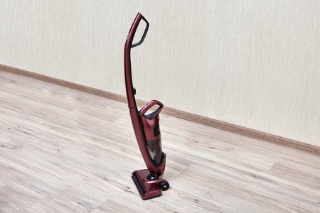 Handheld vacuum cleaner with a separate small dust tank in an empty room. Archivio Fotografico