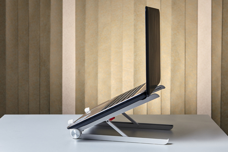 Cooling stand dock desk holder for notebook with open laptop, side view. Stock fotó