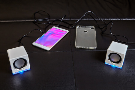 On sofa lies smartphone to which small white cubic-shaped speakers made of plastic and equipped with blue LED light are connected with cable, and silicone case for smartphone is located next to it.