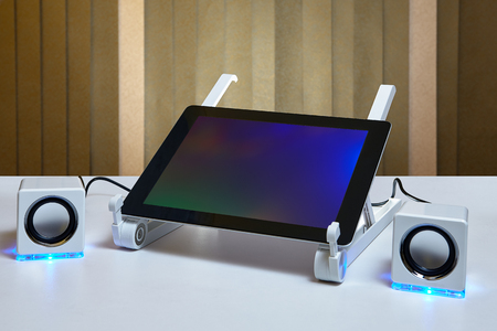 Tablet PC is connected to small external speakers.