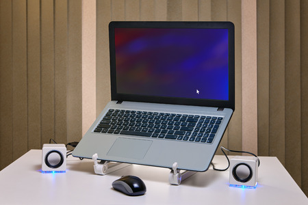 An runned notebook on a cooling rack and two small white USB speakers with an blue LED lights.