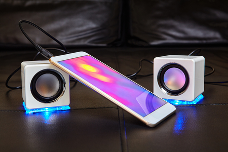 A smartphone with a bright color display is connected to small speakers with a cable. 写真素材