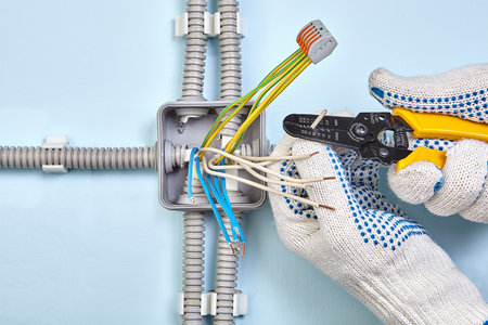 An electrician is stripping of wire insulation using a wire tool.