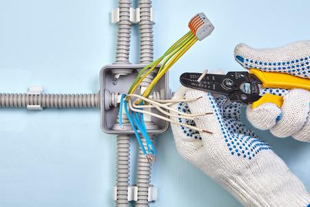 Un elettricista sta spellando l'isolamento del filo usando uno strumento per fili.
