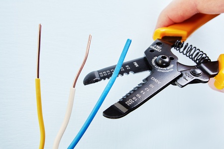 Electrician uses the wire stripper cutter to remove of insulation from the tip of each of the wires during electrical wiring services, close-up. Standard-Bild