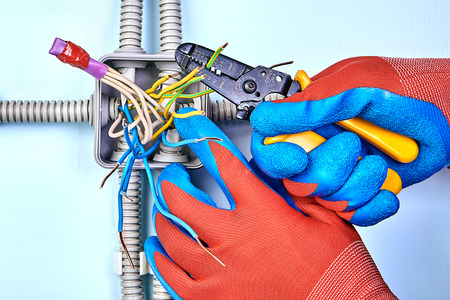Installation of surface mounted  junction box, electrician uses the wire strippers to remove of insulation from the tip of each of the wires.