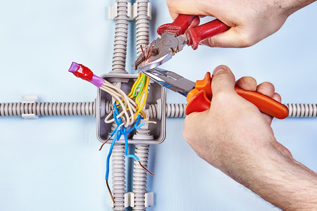 Worker is tightening wires together for good contact with needle-nose pliers.