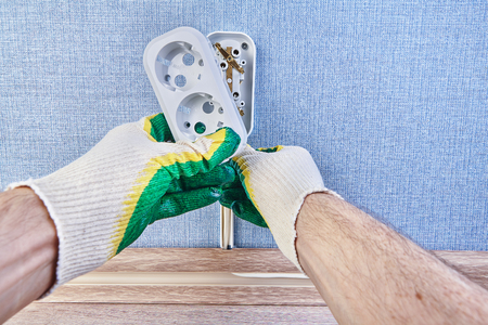 Worker is putting new           pattress box on wall outlet,  installing euro wall plug socket. Фото со стока