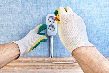 Closeup of changing pattress box of wall outlet with help of screwdriver by electrician in protective gloves.