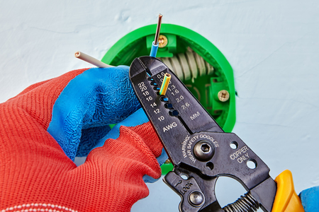 Worker in protective gloves  is removing insulation from wires of round outlet box with wire stripper tool. Фото со стока