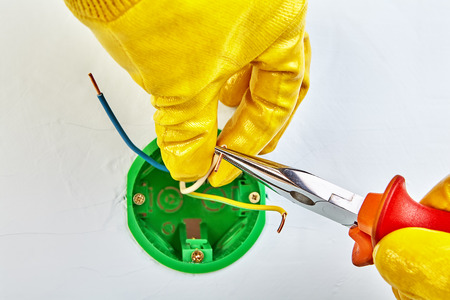 Cutting ends of copper wiring with electrical pliers by electrician in yellow protective gloves, electrical work.
