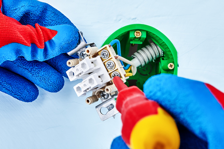 Worker in protective gloves is tightening screw in light switch with hand tool. Stock Photo