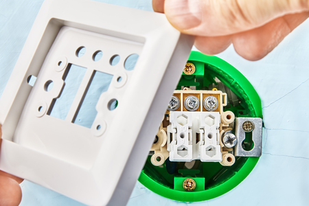 Worker is putting part of european push button on round electrical box, electric installation work.