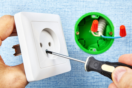 Electrician is tightening screw in new european standard socket with screwdriver, electrical installation.