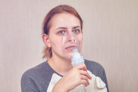 Woman, who has COPD, is doing inhalation with help of nebulizer chamber, she is breating through with it. Stock Photo