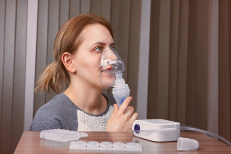 Girl with idiopathic pulmonary fibrosis is breathing with nebulizer chamber, there are compressor nebuliser system and medicines on the table.