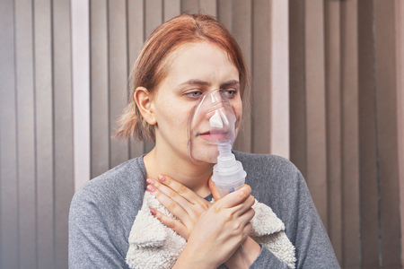 Young woman has an asthma attack and uses nebulizer chamber for patients with interstitial lung disease to stop it. Stock Photo