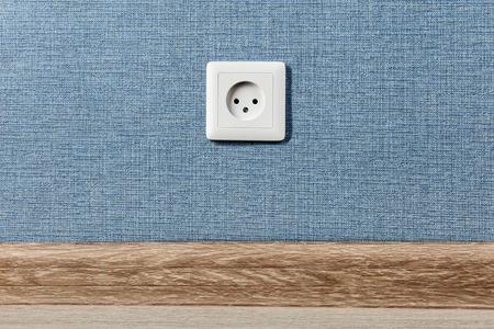 Presa elettrica Euro tipo C, punto di alimentazione elettrica in casa, sullo sfondo della parete blu.