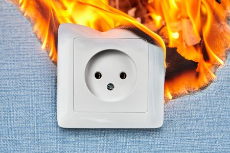 Apartment fire is caused by electrical outlet faults. Burnt and damaged electric plug socket from overload short circuit. Banco de Imagens