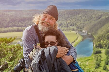Ecological tourism in the wild highlands, father hugs his daughter on the top of a cliff against the background of a coniferous forest and a quiet river.