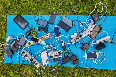 A lot of batteries, chargers for smartphones and electrical extension cords with electric devices, screens up, which are charged by them, they lie on a tarp on the grass.