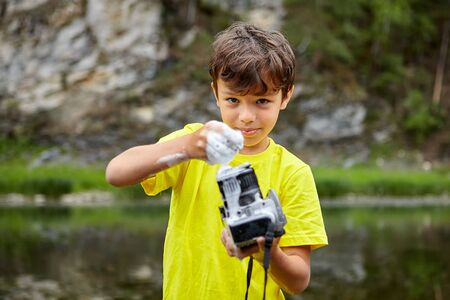 White boy in yellow T-shirt is covering digital camera by foam and going to wash it being on nature. Stock Photo