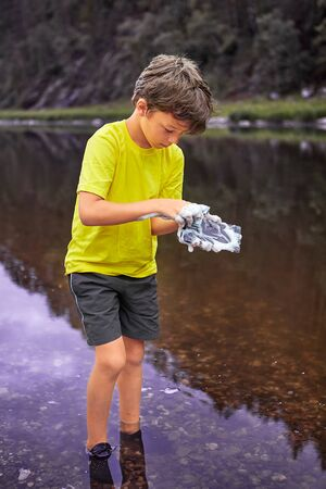 White wet  boy about 8 years old is standing in river and washing mobile phone using foam of soap, he is in water.