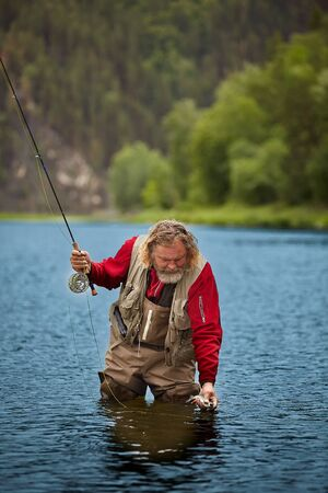 Mature bearded whire wet man is watching at fis, which he has caught by fly-fishing, he is in waterproof clothing, eco-tourism.