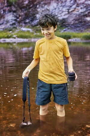 White pretty smiling boy about 8 years old is standing in river with digital camera partly in water, he is cheerful.