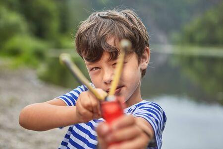 El niño matón blanco de unos 8 años está jugando con tirachinas en el parque y se está preparando para disparar.