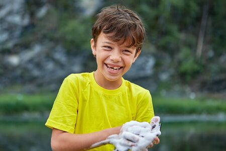 White cheerful boy about 8 years old is standing in rivers water and washing digital camera using foam of soap, he is smiling. Stock Photo