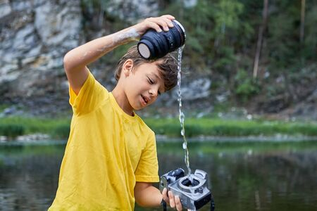Cheerful white hooligan boy is spoiling digital camera by watering it in river, it makes him fun. Stock Photo - 128260294