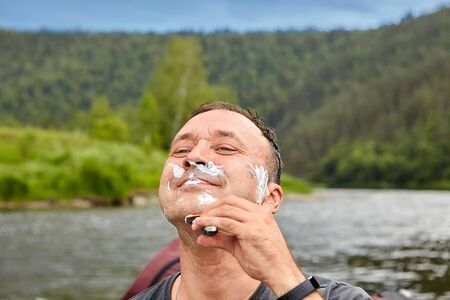 Smiling man shaves in nature using shaving foam and a razor. 스톡 콘텐츠