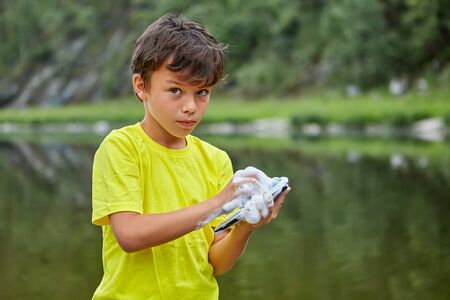 A serious boy is washing a mobile phone with soap while standing in the riverbank. The child ruined  parents gadget by wetting it .