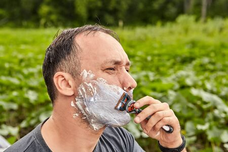 A mature man shaves outdoors using shaving foam and a razor.