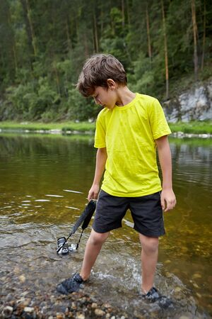 A young bully indulges in the camera of his parents. The boy drowned the camera in the river, and the gadget fell into disrepair, as it was flooded with water.