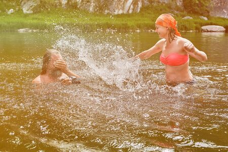 Young pretty woman in swimsuit is making mature man and his camera wet while swimming in the river. Standard-Bild - 129363248