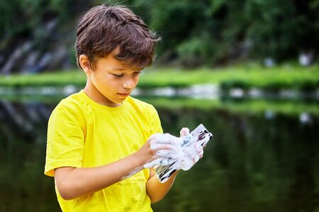 Removing dirt from the screen of a mobile phone. Little boy cares for a smartphone screen using soap suds and river water. The child is playing with a cellphone in nature, the phone is wet and broken.